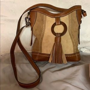 Tan and brown over the shoulder purse with tassel.